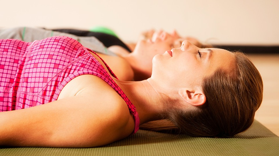 A woman lying in savasana relaxation after yoga, a great way to relieve stress