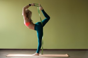 Yoga Props: a woman practising dancer pose natarajasana with a belt