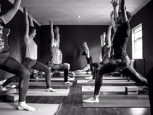 Durga yoga teacher trainees in Warrior One pose, March 2018.